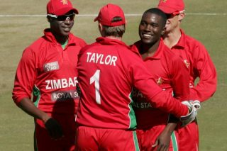 Zimbabwe's Elton Chigumbura (R) celebrates a wicket with Vusimuzi Sibanda (L) and teammates. - ICC T20 News