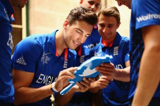 Steven Finn uses a twitter mirror as James Taylor watches on.