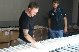 Brendon McCullum signs bats during New Zealand's media session as Daniel Vettori looks on.