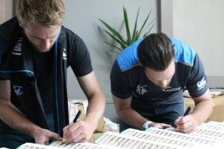 New Zealand players sign bats during the team's media session.