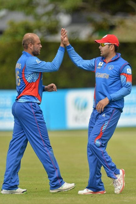 Mirwais Ashram and Mohammad Nabi, Afghanistan, celebrate a catch against Oman.