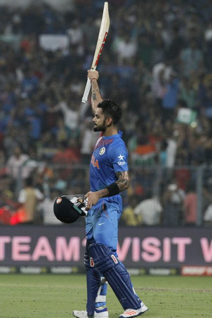 Virat Kohli raises his bat after his half century.
