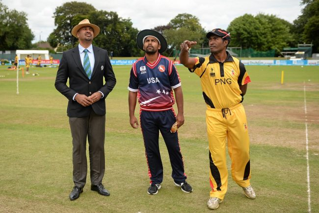 Match referee Graeme Labrooy with team captains Muhammad Ghous, USA, left, and Jack Vare, PNG, during the coin toss.