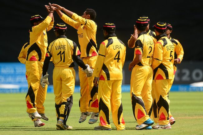 Charles Amini of PNG celebrates with team-mates after taking a wicket.