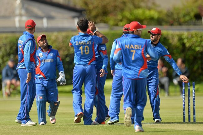 Afghanistan players celebrate after taking the first Oman wicket.