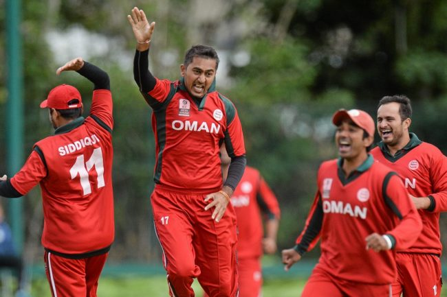 Rajeshkumar Ranpura of Oman celebrates a wicket with teammates.