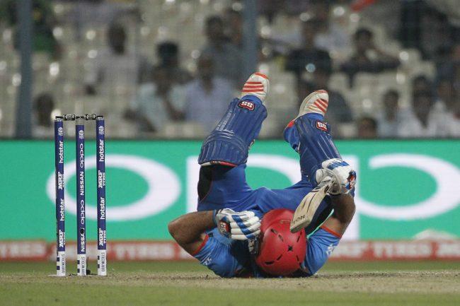 Samiullah Shenwari of Afghanistan slips and falls after hitting a shot against Sri Lanka.